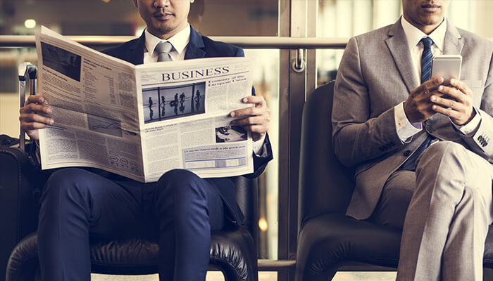 two men in suits newspaper and mobile